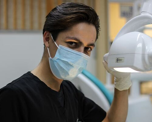 man-with-mask-holding-dental-glass